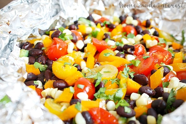 Fresh summer vegetables including sweet corn and tomatoes grilled in a foil packet and tossed in a lime vinaigrette. .
