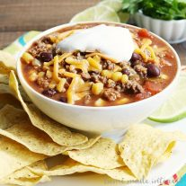 This slow cooker taco soup is one of the best comfort foods for the summer, fall, or winter. Loaded with ground beef, black beans, and Tex-Mex spices, topped with sour cream, and cheese, and scooped up on tortilla chips. This is the BEST taco soup made in a Crock Pot. Serve it on game day or as an easy weeknight dinner for families. #taco #soup #comfortfoods #slowcookerrecipes #crockpotrecipes #homemadeinterest