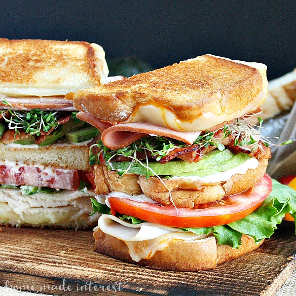 An amazing grilled cheese recipe for National Grilled Cheese Month! We've taken a California Club sandwich and turned it into a triple decker grilled cheese sandwich. This grilled california club sandwich oozes Munster cheese, and is piled high with ham, turkey, bacon, avocado, lettuce, tomatoes, and sprouts.
