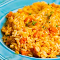 Carrot Orzo | This easy carrot orzo is flavored with carrot juice and cooked like a risotto recipe using orzo pasta inside of rice. This simple side dish would make a beautiful Easter side recipe. Carrot Orzo is a spring recipe full of bright flavors!