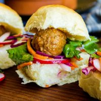 Single Banh Mi slider with meatball on pickled radish, carrots, cucumbers, and red cabbage.