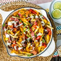 Loaded Steak Fries | These Loaded Steak Fries are the perfect party appetizer recipe especially if you're looking for easy game day recipes or football party food. A big skillet loaded with french fries and grilled steak and covered in cheese and ranch dressing. This is an easy appetizer recipe that anyone can make and a steak recipe that everyone will love!