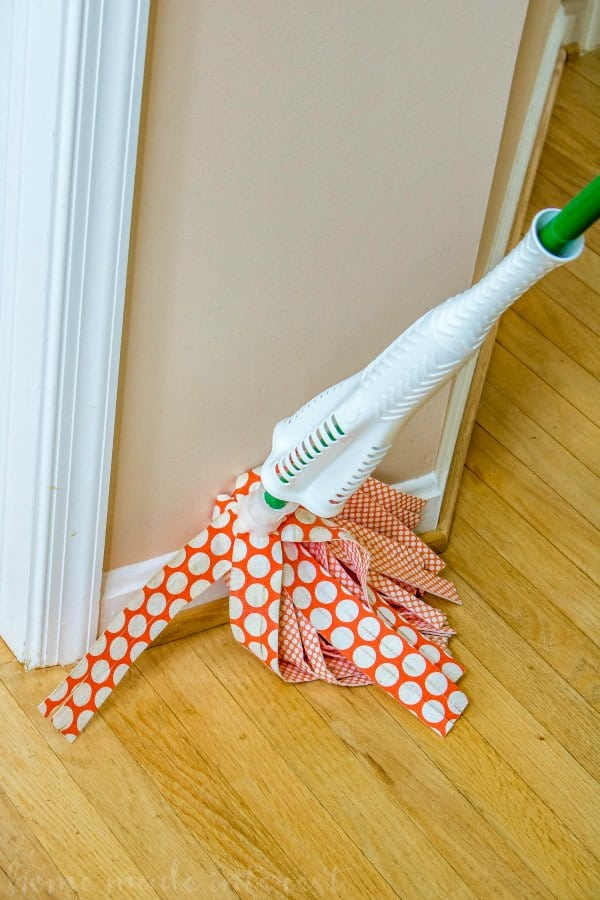 cleaning the baseboards with a mop