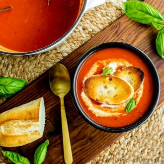 A top down photo of roasted red pepper soup topped with toasted baguettes.