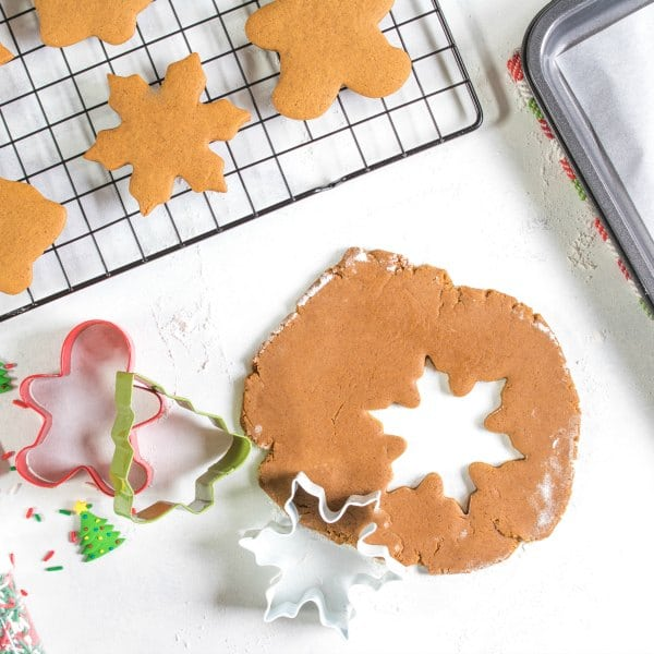 Soft gingerbread cookie dough rolled out with a snowflake cut out of it.