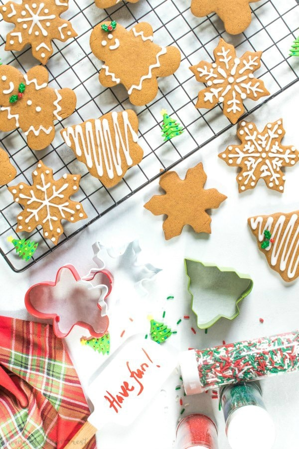 Gingerbread cut-out Christmas cookies shaped like gingerbread men and gingerbread women, snowflakes, and Christmas trees cooling on a cooling rack.