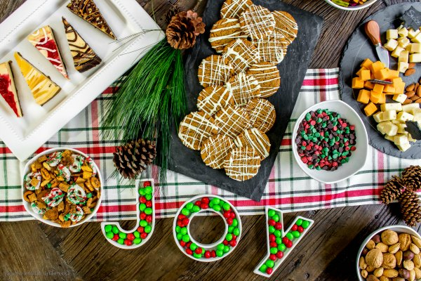 Christmas table with cookies, cheesecake and cheese platter