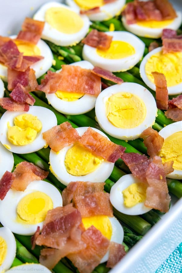 bacon and hard boil egg slices on top of asparagus