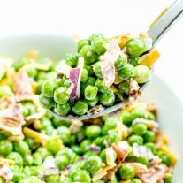 Creamy Bacon Pea Salad being scooped out of a bowl with a spoon.