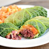 A corned beef cabbage roll cut open with corned beef and carrot parsnip filling