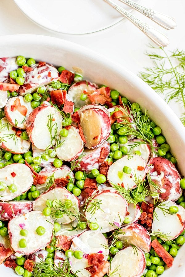 English Pea and Potato Salad in a large white bowl with sprigs of dill.