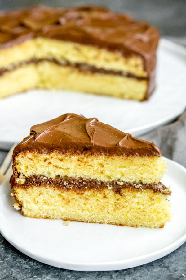 Slice of two layer yellow butter cake with chocolate frosting sitting in front of the whole yellow butter cake