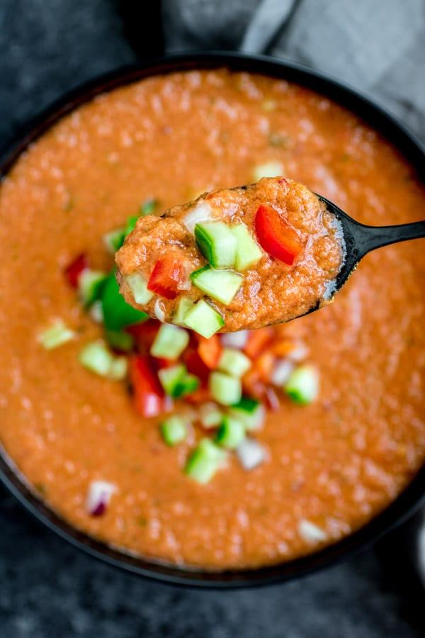 spoon full of Gazpacho Soup in a bowl