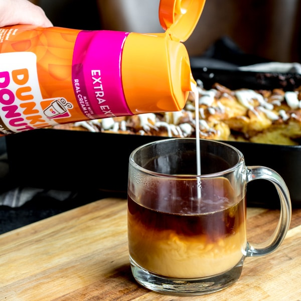 pouring Dunkin Donuts creamer into coffee