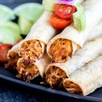 Chicken Taquitos stacked on plate