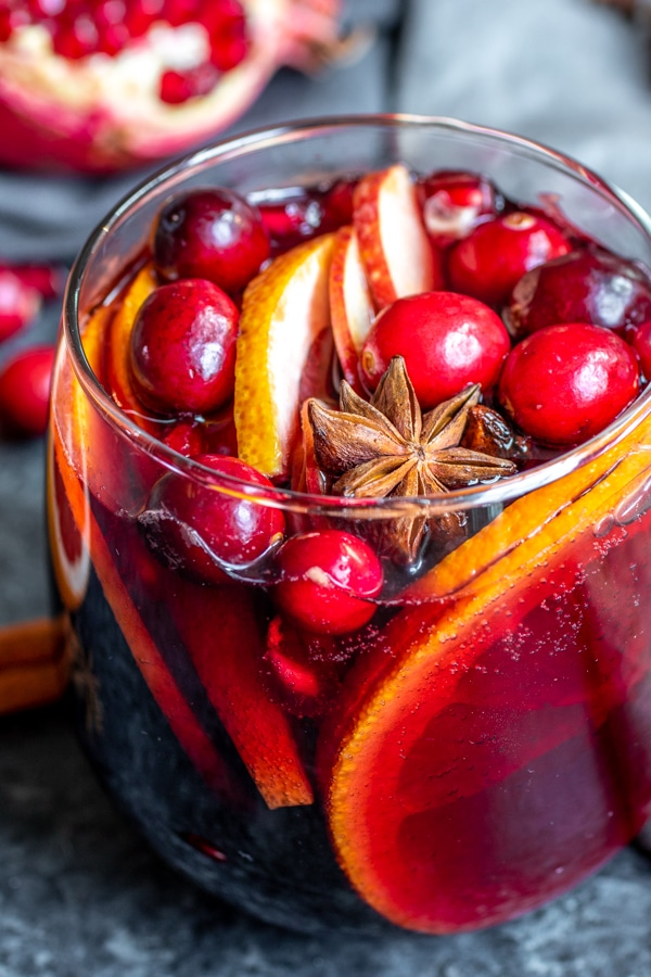 A close up of a star anise pod in a glass of Winter Red Wine Sangria