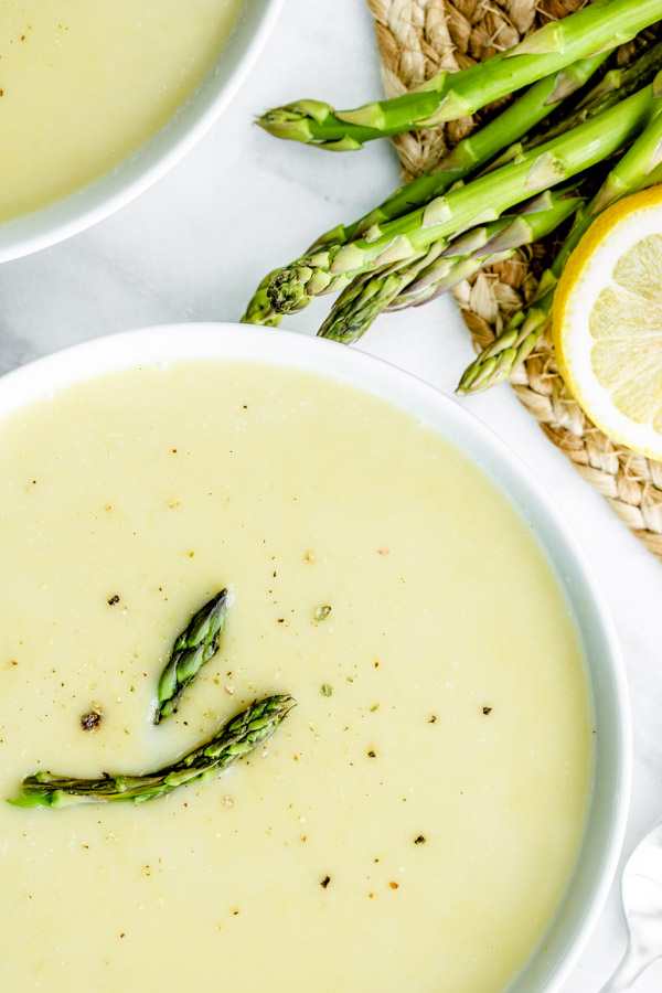 bowl of Creamy Asparagus Soup topped with fresh asparagus