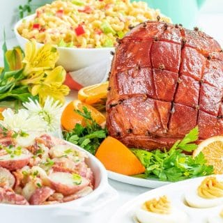 Honey glazes ham on a table with sides