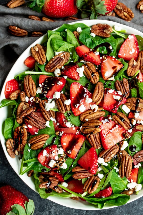 Strawberry & Spinach Salad topped with pecans and goat cheese
