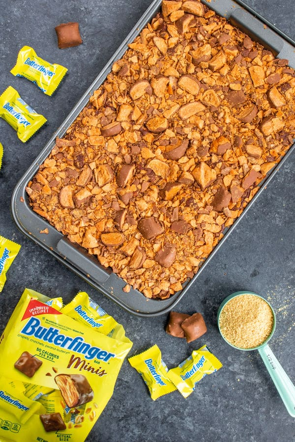 adding the topping to Butterfinger S'mores Bars