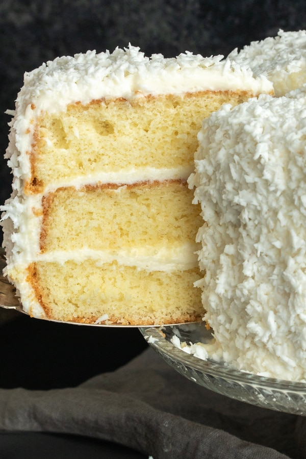 Slice Of Coconut Cake Being Cut From A Three Layer