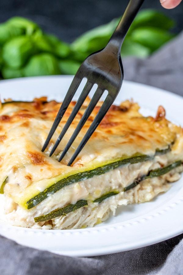 Fork going in for a big bite of Chicken Alfredo Zucchini Lasagna